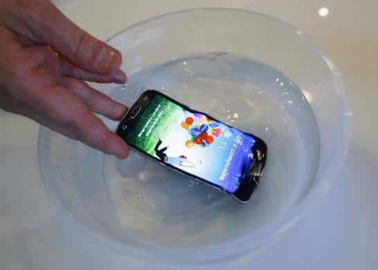 P2i's CEO Carl Francis demonstrates a mobile phone functioning in water, during an interview in Singapore