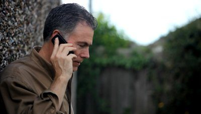 stock-footage-a-man-outside-using-wireless-service-to-chat-with-someone-via-his-cell-phone